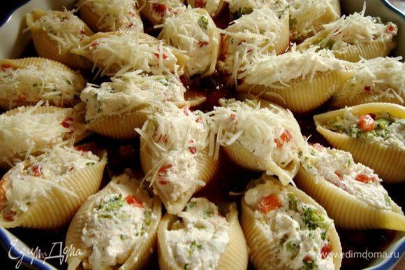Соус капоната вылить в большое(пасты получается много)жаропрочное блюдо.Конкильони наполнить начинкой и выложить на(в)соус,присыпать оставленным пармезаном,сбрызнуть оливковым маслом и поставить в нагретую до 180*С духовку на 25-30 минут.