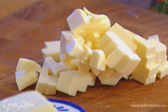 Предварительно охлажденное сливочное масло порубить небольшими кубиками.