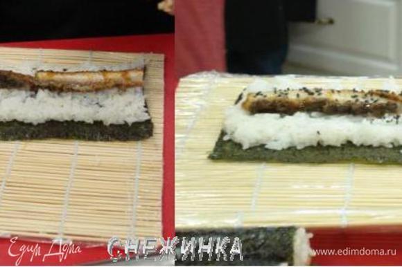 На середину слоя риса кладем 2 полоски угря. Можно немного присыпать черным кунжутом.