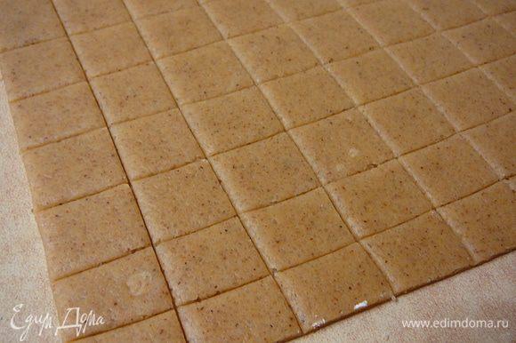 Присыпать рабочую поверхность слегка мукой и раскатать тесто толщиной в 2-3мм.Нарезать тесто на квадратики 2*2см.