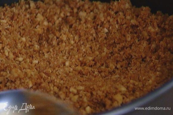 Перемешать растопленное масло и измельченное печенье, равномерно выложить в разъемную форму, слегка утрамбовать и отправить в холодильник.
