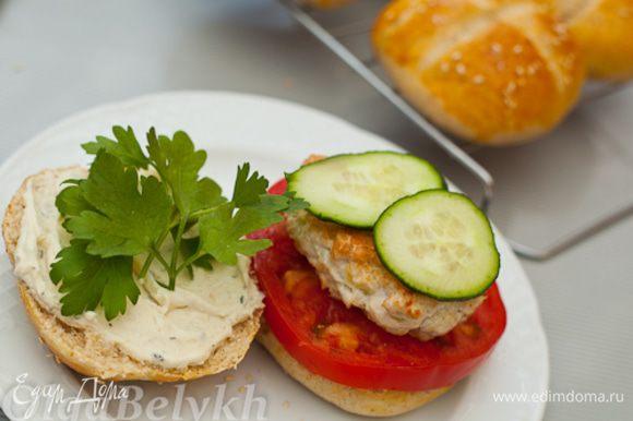 Сверху помидора положить котлету, 2 кружка огурца и листики петрушки. Накрыть второй половинкой булочки. Подавать сразу на стол.