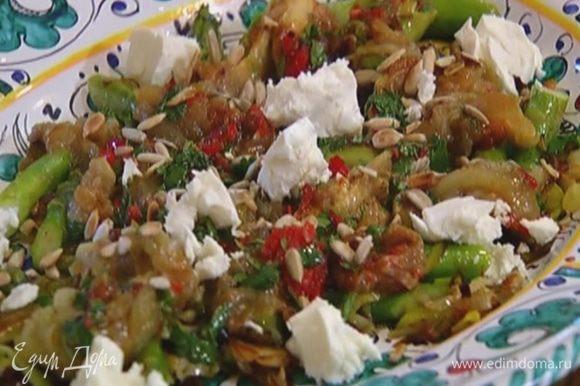 Выложить на блюдо спаржу и лук-порей, затем мякоть баклажана, полить заправкой, посыпать семечками и измельченной фетой.
