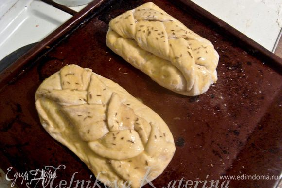 Выложить булки на противень, смазанный сливочным маслом. Накрыть тканью и поставить в теплое и укромное место для расстойки примерно на 20-30 минут. После этого смазать булки яичным желтком, посыпать сверху тмином.