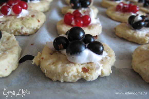 Смазываем каждое печенье небольшим количеством безе, а сверху - по 4-5 ягод смородины. Можно использовать и другие ягоды с кислинкой, по вкусу.