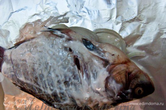На кусок фольги выложить рыбу. Смазать ее сметаной, перевернуть и смазать второй бок.