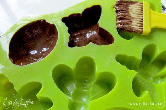 Шоколад растопить в микроволновке. Хорошенько размешать. Силиконовые формы смазать мягким шоколадом. Дать застыть в холодильнике минут 10. Затем намазать второй слой и снова дать застыть. Если нужно, то смазать формы и в третий раз, чтобы слой получился плотным и не просвечивал.