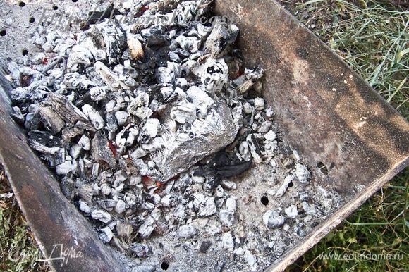 Положить конверт в угли, сверху присыпать также углями и оставить на 30-40 минут. Проверить готовность картофеля, проткнув сквозь фольгу его шпажкой.