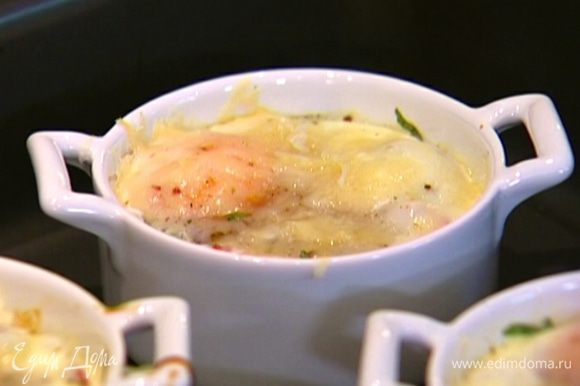 Формочки с помидорами и яйцами поместить в глубокий противень и отправить в духовку на 10 минут, а затем на 2 минуты поставить под гриль.
