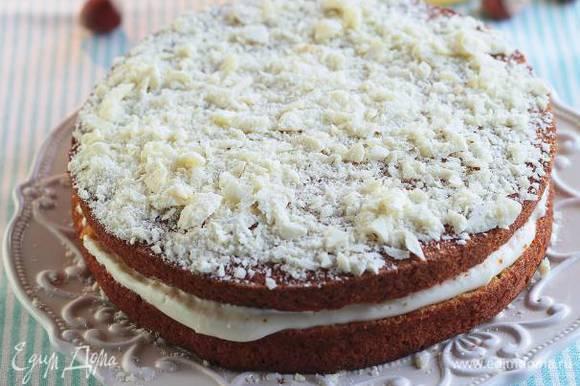 Остывший корж разрезать по толщине пополам, промазать большей частью сметанного крема и снова соединить. Сверху тоже смазать кремом и украсить натертым белым шоколадом.