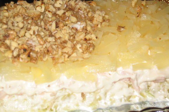 Слой 3: нарезать кольца ананаса и аккуратно их выложить, сверху посыпать орехами и смазать майонезом верх и бока