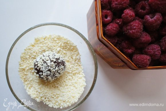 Достать из холодильника шоколадную смесь. Сформировать конфетку, в серединку которой положить малину. Обвалять в крошке белого шоколада.