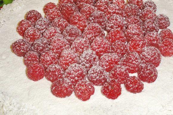 Когда ганаш застынет, украсьте торт ягодами малины и посыпьте сахарной пудрой (по желанию)