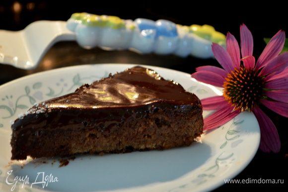 Достанем из формы наш торт, выложим на тарелку, придерживая концы бумаги. Бумага должна легко отойти от торта. Выливаем в центр нашу шоколадную глазурь и лопаточкой разравниваем. Дадим постоять чуток. Поставим в холодильник для застывания глазури или можно подавать сразу, разрезав торт порционно.