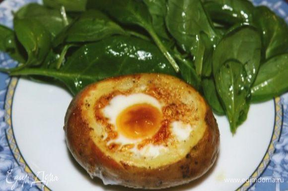 Выложить шпинат на тарелки, рядом поместить запеченный картофель.
