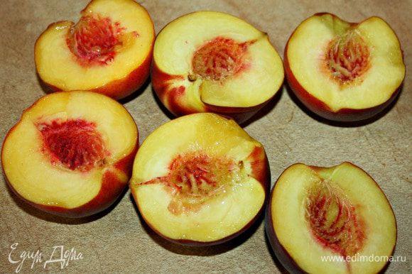 Персики разрезать пополам и вынуть косточки.