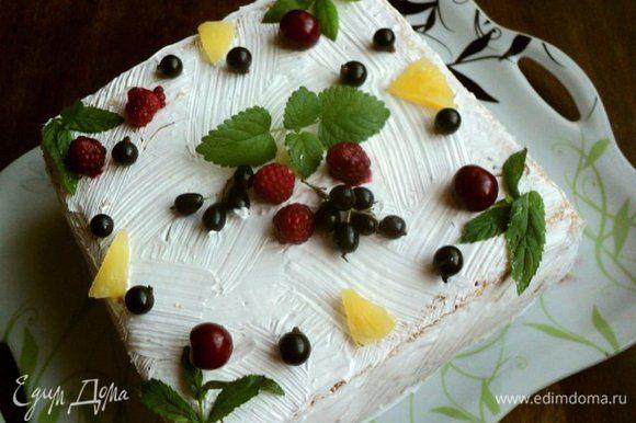 Покрыть взбитыми сливками бока и верх торта, нанести узор (я наносила узор кисточкой). Сверху украсить торт фруктами и листиками мяты.