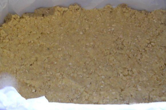 Форму с низкими стенками смазываем маслом и выкладываем в нее половину теста. Я использую бумагу для выпечки, так пирог потом легче достать. Тесто слегка утрамбовываем пальцами.