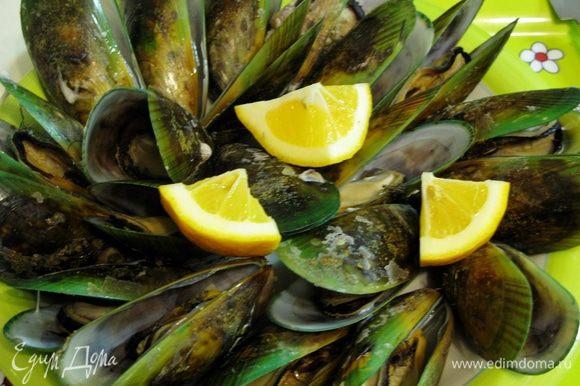Когда мидии откроются, достаем их из воды. Выкладываем на большое блюдо, украшаем четвертинками лимона.