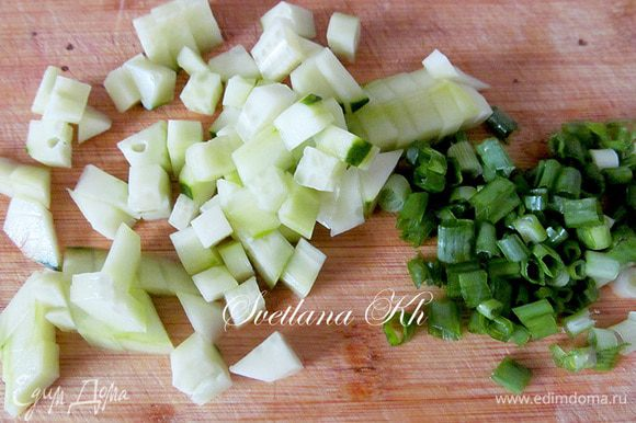 Огурцы и зеленый лук мелко нарезать.