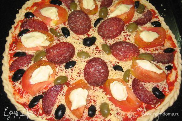 Разложить по поверхности порезанный помидор, колбасу и оливки. На каждый ломтик помидора уложить чайной ложкой плавленный сыр