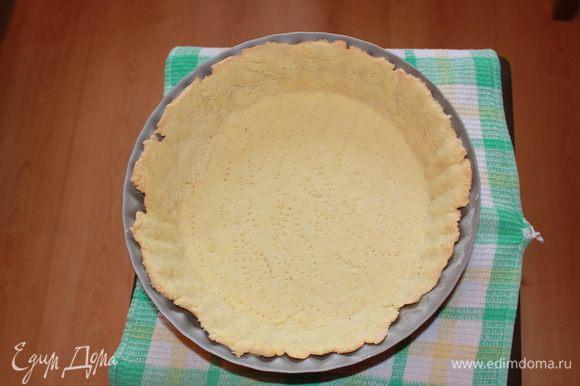 Тесто раскатайте скалкой на рабочей поверхности, уложите в форму, сформировав бортики. Излишки теста обрежьте. Тесто в нескольких местах наколите вилкой. Сверху уложите кулинарный груз (пергамент и бобы, возможно рис, горох) Запекайте в разогретой до 200 гр. духовке 10 минут. Затем аккуратно снимите груз и держите в духовке еще 7 минут до золотистого цвета.