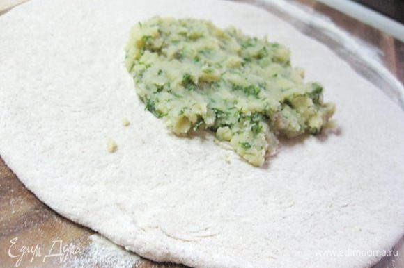 Теперь приступаем к лепке лепешек. Взять половину теста, раскатать его в небольшую лепешку (не тонко! из этого куска теста получится в итоге большая лепешка по размеру сковороды, а на этом этапе вы должны раскатать ее в два раза меньше). Положить в центр немного картофельной смеси.