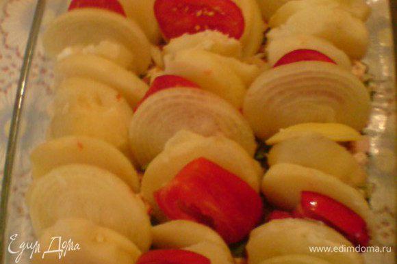 Сверху вертикально разложить картошку, немного вставляя ее в фарш. Между картошкой повставлять кольца лука и ломтики помидоров.