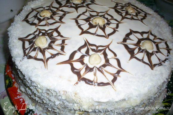 Бока торта обсыпаем смесью измельченных обрезков и кокосовой стружки. Шоколад растапливаем с 1 чайной ложкой сметаны, наполняем корнетик и рисуем по два концентрических круга. Затем зубочисткой делаем паутинку., в центр каждой кладем по орешку. Отправляем торт в холодильник, желательно на ночь. Приятного аппетита!