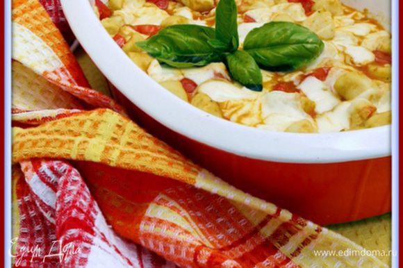 Перенести ньокки с соусом в форму для выпечки. Подмешать часть сыра к ньокки, а часть распределить по поверхности. Запекать при 200° около 5 минут или пока сыр не расплавится.