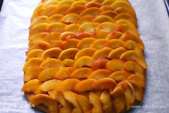 На пирог черепицей разложить ломтики персиков.