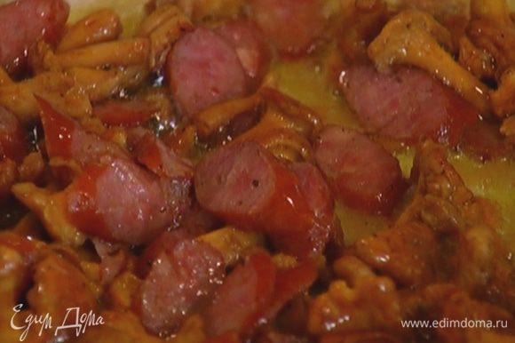 Колбаски порезать маленькими кусочками, добавить к грибам, перемешать и обжарить все вместе.