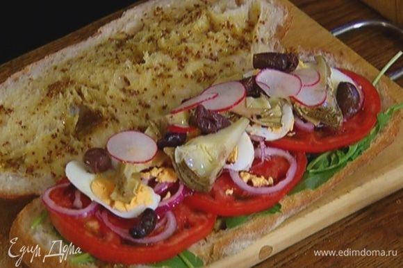 На одну половину хлеба слоями выложить руколу, нарезанные помидоры, редиску, лук, яйцо, артишоки и оливки.