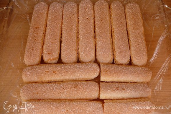 Форму выстелить пищевой пленкой, выложить слой бисквитного печенья.