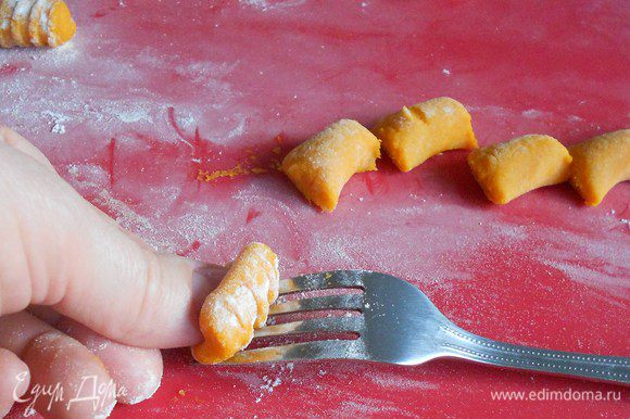 Прокатать каждый кусочек теста по тыльной стороне вилки, слегка надавливая на него большим пальцем, от основания зубцов к острию. Не забывайте слегка обваливать кусочек в муке, чтобы не прилип к вилке. Получится как бы свёрнутый пласт теста с ребристой поверхностью снаружи. Это самая утомительная часть приготовления блюда. Можно оставить ньокки в виде цилиндров, можно сплющить их вилкой и тогда получатся шайбочки с одной ребристой стороной, можно скатать шарики и большим и указательным пальцами сжать каждый с двух сторон. Хороши все варианты.