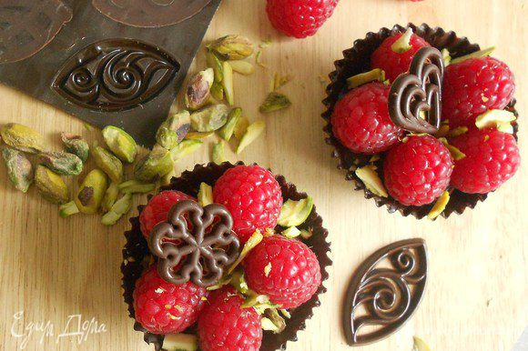 Выложить ягоды в корзинки, посыпать фисташками, при желании украсить готовыми шоколадными фигурками.