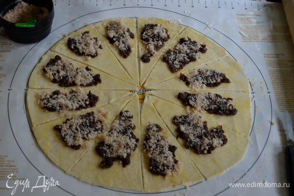 Раскатаем тесто в круг на припыленной поверхности мукой.Разрежем на 12 или 16 частей.Смажем яйцом поверхность,выложим начинку.