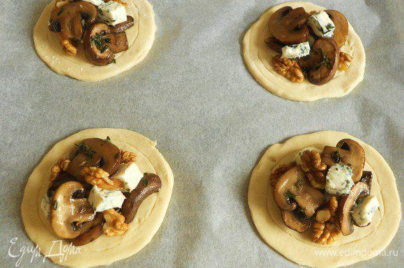 Смешать грецкие орехи, кусочки сыра с грибами и ложкой выложить начинку в середину каждого круга. Кистью смазать края взбитым яйцом.