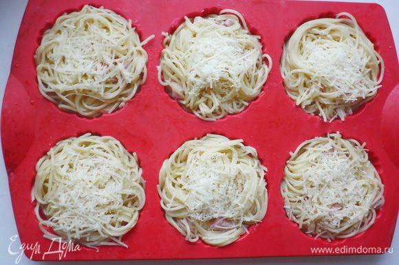Форму для кексов (тарталеток) смазать растительным маслом. Спагетти с соусом выложить в формочки. Сверху посыпать оставшимся сыром. Запекать в разогретой до 180 г духовке в течение 20 мин (т к я использовала силиконовую форму и ставила ее в холодную духовку, то потребовалось еще дополнительно 10мин).