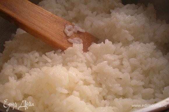 Снять кастрюлю с огня и дать рису постоять 20 минут с закрытой крышкой. Затем легкими движениями распушить рис деревянной лопаткой, пока он горячий.