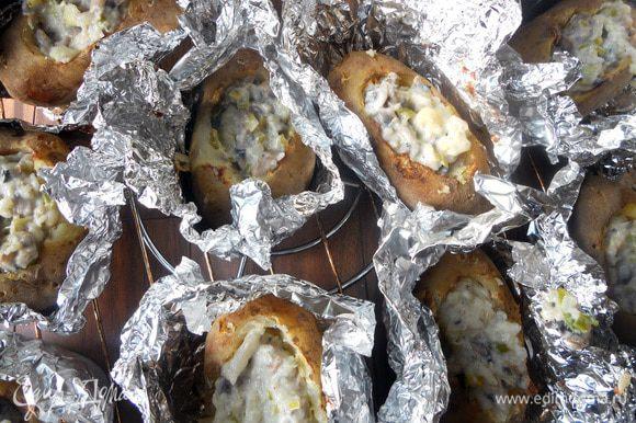 Картофель наполнить получившейся начинкой, сбрызнуть оливковым маслом.Снова завернуть фольгой (можно не плотно) и поместить в духовку минут на 20. После чего раскрыть фольгу, присыпать картофель тертым сыром, при необходимости еще раз сбрызнуть маслом (по кусочку сливочного будет совсем уместно, но не агитирую) и вернуть в духовку еще на 10 минут, или пока сыр на расплавится.