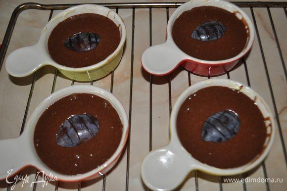 Разогреть духовку до 180°С. Смазать маслом формы для выпекания. Распределить по ним шоколадное тесто. В каждую форму положить половинки слив. Поставить в духовку и выпекать 25 мин.