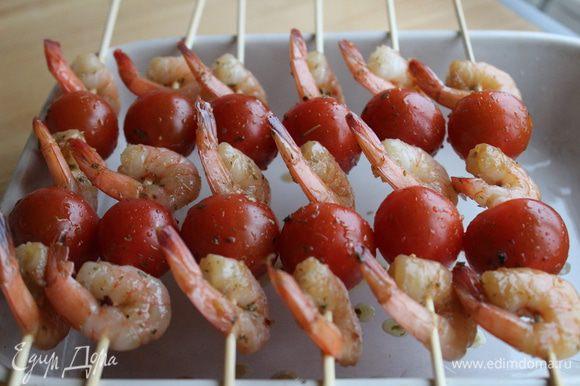 Деревянные шпажки предварительно замочить в холодной воде на 10-15 минут. Нанизать креветки и помидоры. Запекать в духовке 20 минут. Подавать горячими.