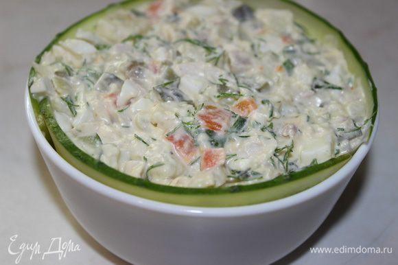 Огурец нарезать вдоль тонкими пластинками, уложить их по краю формы (пиалы)... заполнить форму салатом, немного утрамбовав его ложкой