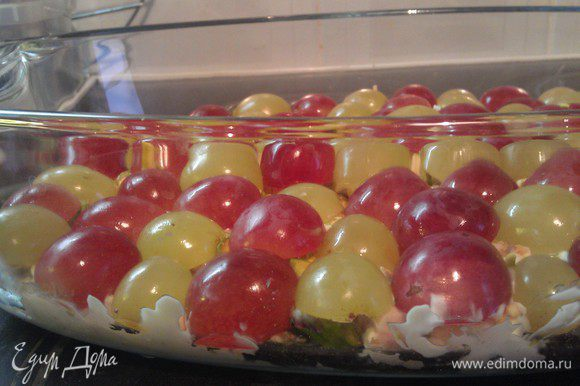 Следующим слоем выложить по всей поверхности половинки винограда, чередуя между собой красный и белый виноград.