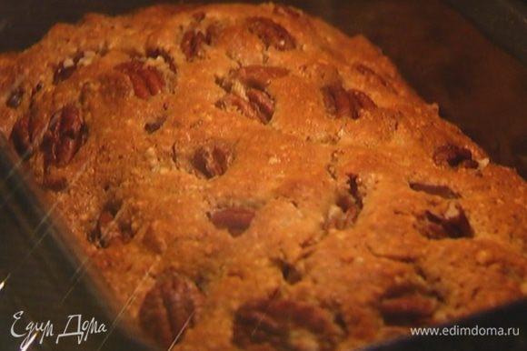 Продолговатую форму для выпечки смазать растительным маслом, выложить тесто, вдавить в него кусочки шоколада, сверху разложить орехи, слегка прижав их.