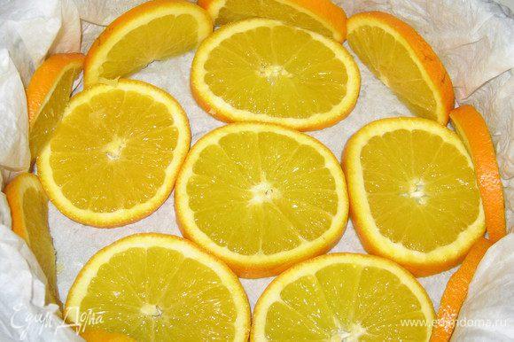 Бумагу для выпечки намочить и хорошо отжать. Выстелить форму бумагой для выпечки, дно и бока формы выложить кружочками апельсинов.