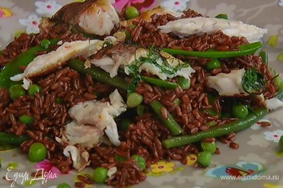 На большую тарелку выложить рис с овощами, сверху поместить рыбное филе.