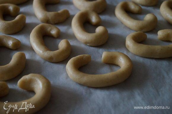 Из теста скатать колбаску и разделить ее на небольшие части, придать им форму полумесяца