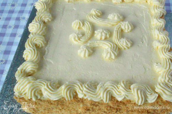 Остатки белого крема добавить в миску с отложенным ранее взбитым маслом, нанести часть полученной смеси на верх торта, выровнять. Остальное выложить в кондитерский мешок. Бока торта обсыпать бисквитной крошкой.Иногда обсыпали рубленными грецкими орехами. Из мешка нанесите украшения.